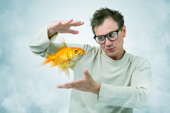 Mad Professor in smoke and goldfish, art concept of science Stock Photos
