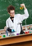 Mad professor stares at Bunsen flask. With yellow liquid Stock Images