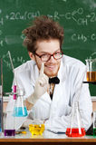 Mad professor surrounded with chemical glassware Royalty Free Stock Photos