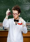 Mad professor wonders at the flasks. With colored liquid Royalty Free Stock Image