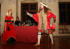 Mad Renaissance Man. Long haired angry man in red renaissance costume pointing somebody with a worried queen behind as a summer 2015 performance at Svihov Water Stock Image