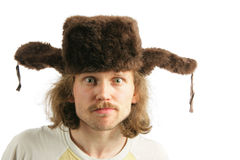 Mad russian. Man with ear-flaps cap lookng at camera isolated over white background Royalty Free Stock Image
