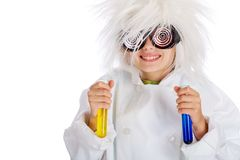 Mad Scientist. A child dressed as a crazy mad scientist with funny glasses and a wild white hair style holding a blue and a yellow beaker in a laboratory Royalty Free Stock Photography