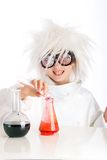 Mad Scientist. A child dressed as a mad scientist pours a bubbling red liquid into a beaker during a dangerous experimant in an all white laboratory Royalty Free Stock Photography