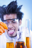 Mad scientist. A mad scientist doing an experiment with sticking out tongue in laboratory Royalty Free Stock Photo