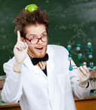 Mad scientist with an apple on his head. Mad scientist with a green apple on his head shows forefinger while handing molecularmodel Stock Photo