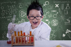 Mad scientist with chemical fluid. Mad little scientist doing experiment with chemical fluid and looking at camera Royalty Free Stock Images