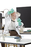 Mad scientist conducts chemistry experiment. Cheerful mad senior scientist in lab measures green liquid in beaker. Frizzy grey hair, round glasses, lab coat Stock Image