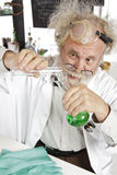 Mad scientist conducts chemistry experiment. Mad senior scientist in lab concentrates on pouring green liquid into beaker. Frizzy grey hair, round glasses, lab royalty free stock photos