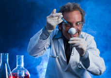 Mad Scientist with Golf Ball and Hypodermic Needle. A mad scientist uses a hypodermic needle during an experiment to improve a golf ball Royalty Free Stock Images
