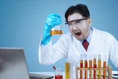 Mad scientist in laboratory. Male crazy asian scientist doing research with laptop computer and chemistry fluid Royalty Free Stock Photo
