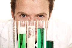 Mad scientist look over test tubes close. A man is looking over the top of several test tubes Royalty Free Stock Image