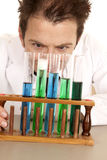 Mad scientist look at test tubes Royalty Free Stock Photography