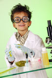Mad Scientist in Slime. A preschooler with wild hair in lab coat, coke-bottle glasses and gloves, happily working with slipery green slime on a glass table with stock images