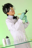 Mad Scientist Taking Notes. A young mad scientist in protective garb taking notes on a green clipboard Stock Photos