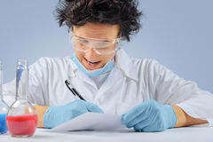 Mad scientist writes. Mad scientist in glasses writes notes of experiment Stock Images