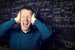 Mad teacher. Stressed teacher portrait and blackboard background royalty free stock photo