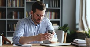 Mad unhappy businessman feeling annoyed using smart phone in office