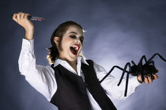 Mad vampire boy prepared to stab a spider. Boy dressed up as a vampire for halloween party, shouting while prepared to stab a spider toy with bloody knife Royalty Free Stock Photos