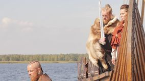 Mad vikings on the Drakkar on the river shore stock video footage