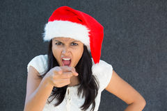 Mad woman. Closeup portrait, cute Christmas woman with a red Santa Claus hat, white dress, pointing at camera, is that you expression, negative human emotion Royalty Free Stock Images