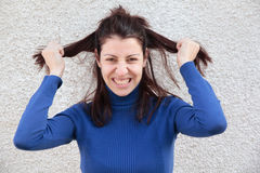 Mad woman pulling hair. Mad young woman pulling her hair with hands in front of grey wall Stock Images