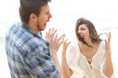 Mad woman shouting to her boyfriend. Ugly and crazy women shouting to her scared boyfriend outdoors on the beach Stock Images