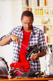 Mad young African Ecuadorian male Technician repairing a toaster with his screwdriver.  Royalty Free Stock Photo