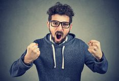 Mad young man screaming loudly. Young angry man in a hoodie shouting in rage looking at camera Stock Photos