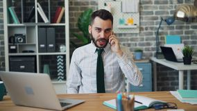 Mad young man yelling on mobile phone gesturing working in office alone. Mad young man is yelling on mobile phone gesturing working in office alone sitting at stock footage