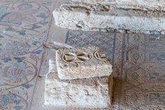 The fragment of mosaic and a stone with a cross carved on it in the covered pavilion on the historical archaeological site Umm ar- stock photo