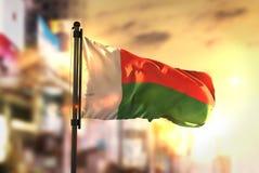 Madagascar Flag Against City Blurred Background At Sunrise Backl Stock Image