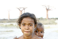 Madagascar-shy and poor african girl with infant on her back Stock Photo