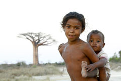 Madagascar-shy and poor african girl with infant on her back. Poverty royalty free stock image