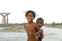 Madagascar-shy and poor african girl with infant on her back Royalty Free Stock Photos