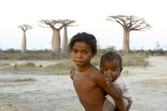 Madagascar-shy and poor african girl with infant on her back. Poverty royalty free stock images