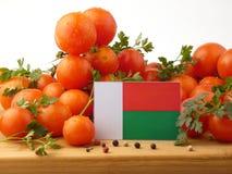 Madagaskar-Flagge auf einer Holzverkleidung mit den Tomaten lokalisiert auf einem wh Lizenzfreie Stockfotografie