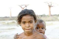 Madagaskar-schüchternes und armes afrikanisches Mädchen mit Kind auf ihr zurück lizenzfreie stockbilder