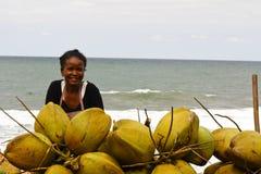 Madagassische Frau, die Kokosnüsse auf dem Strand verkauft Lizenzfreies Stockfoto