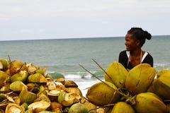 Madagassische Frau, die Kokosnüsse auf dem Strand verkauft Stockfotografie