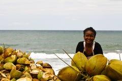 Madagassische Frau, die Kokosnüsse auf dem Strand verkauft Stockbild