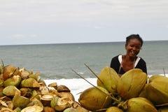 Madagassische Frau, die Kokosnüsse auf dem Strand verkauft Stockbilder