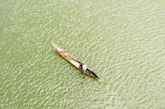 Madagassischer Dachsparrenmann, der traditionelles Kanu rudert Lizenzfreie Stockfotos