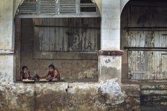 Madagassiska pojkar som äter bröd på en förstörd byggnad royaltyfria foton