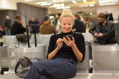 Madame à l'aide du téléphone intelligent tout en attendant aux portes de départ d'airpot Images stock