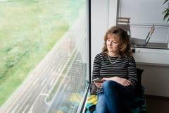 Madame à la maison s'asseyant près de la fenêtre et de la détente Photo stock