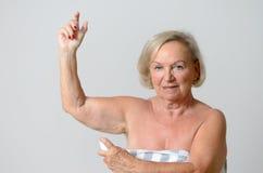 Madame âgée par milieu Applying Deodorant sur l'aisselle Image libre de droits