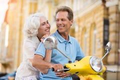 Madame étreint l'homme sur le scooter photo stock