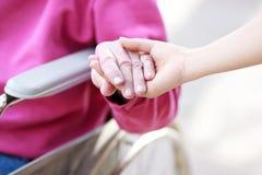 Madame aînée dans des mains de fixation de fauteuil roulant Photo stock