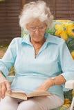 Madame aînée Reading In The Garden Images stock